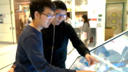 Two Asian men looking on the floor plan of department store
