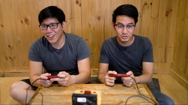 zi ms två asiatiska män spelar gamla hederliga video spel - computer game control bildbanksvideor och videomaterial från bakom kulisserna