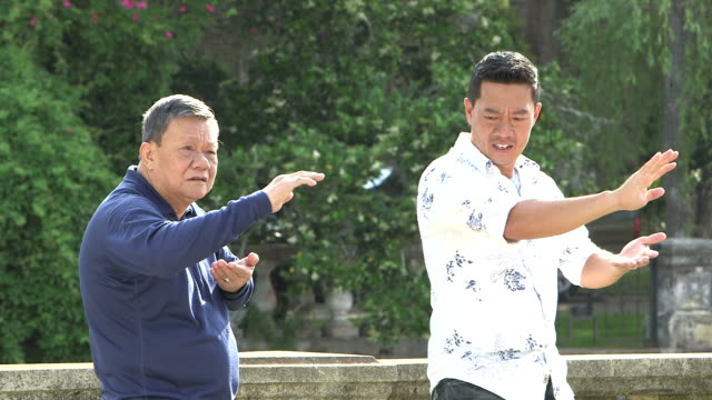 Two Asian men practicing tai chi in the park