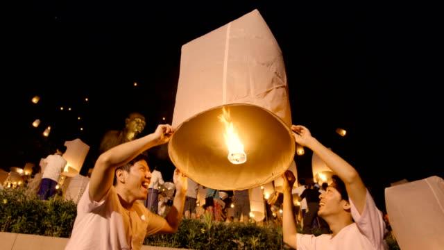 two asian men setting off a sky lantern - lanterna attrezzatura per illuminazione video stock e b–roll