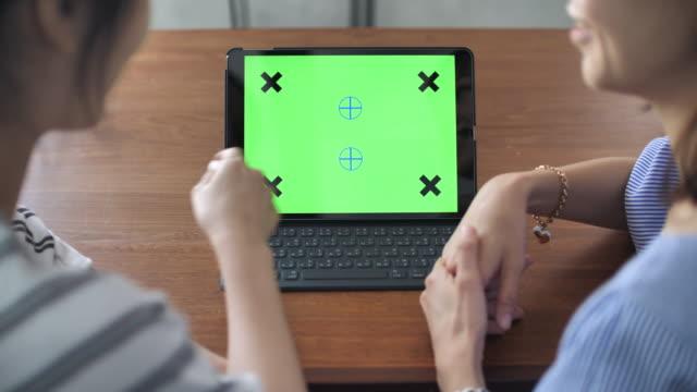 Twee Aziatische mensen met behulp van Tablet PC met groen scherm