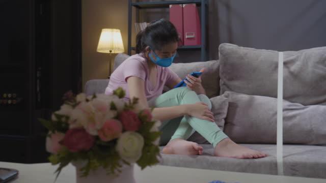 vidéos et rushes de deux soeurs asiatiques jouant le téléphone intelligent dans le salon avec tape une ligne au milieu du sofa à la maison. réduire les concepts de propagation des germes - frère