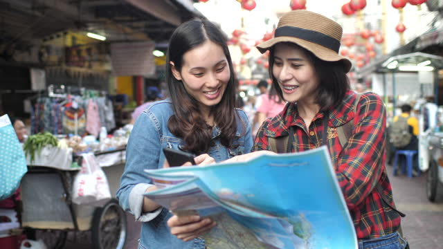 two asian tourist friend using map in guide book in the city - city break stock videos & royalty-free footage