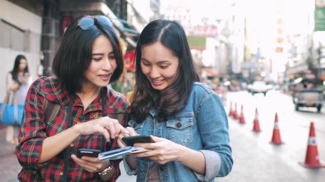 地図付きスマートポネを使用して2人のアジアの観光客 - 見つける点の映像素材/bロール