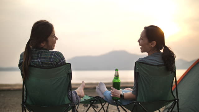 two asian woman friend resting together in camping vacation near lake - picnic stock videos & royalty-free footage