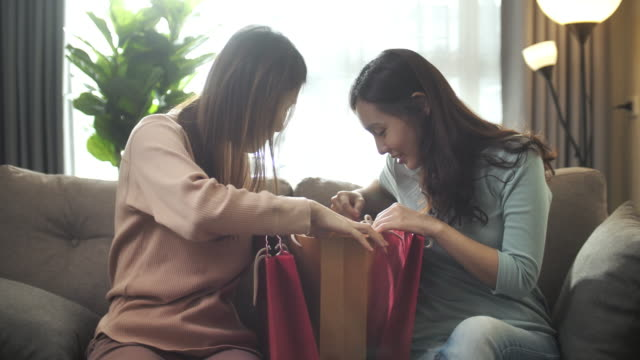 two asian woman friend showing shopping bag at home - shopping bag stock videos & royalty-free footage