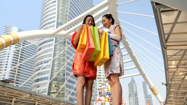 stockvideo's en b-roll-footage met twee aziatische vrouw in chinese jurk boodschappentassen te houden in het centrum van de stad. chinees nieuwjaar en shopping concept - shopping centre