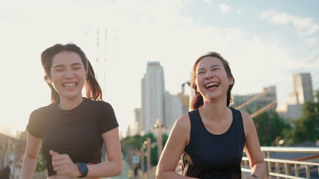 two asian woman jogging and checking her smart watch at public park - positive emotion stock videos & royalty-free footage