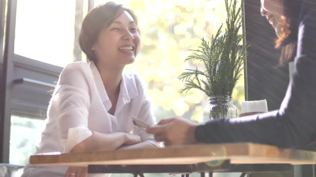 two asian woman sitting in the coffee shop and chatting - comfortable stock videos & royalty-free footage