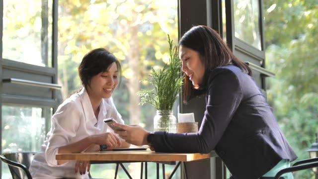 2つのアジアの女性は、コーヒーショップに座って、チャット - 見せる点の映像素材/bロール