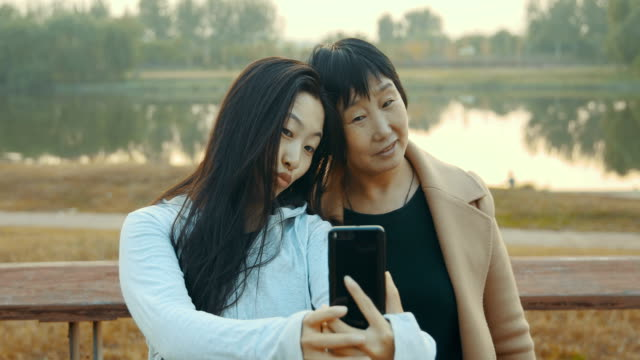 two asian woman taking selfie with phone - adult offspring stock videos & royalty-free footage