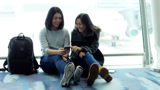 Two Asian Woman Using Smart phone at Departure Airport Terminal waiting for flight