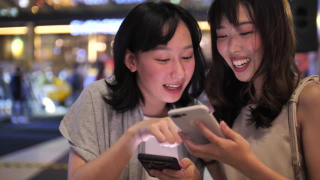 夜にスマートフォンを使うアジア人女性2人、スマートフォンで何かを共有 - text点の映像素材/bロール