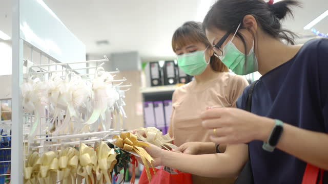 two asian women are shopping the tied bow at the superstore - tied bow stock videos & royalty-free footage