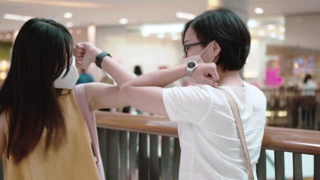 vídeos y material grabado en eventos de stock de dos mujeres asiáticas golpe de codo durante la pandemia de covid-19 - codo