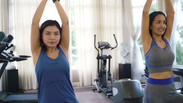 vídeos de stock e filmes b-roll de two asian women in sportswear training exercise and practicing yoga with instructor coach for healthy lifestyle. - equilíbrio vida trabalho