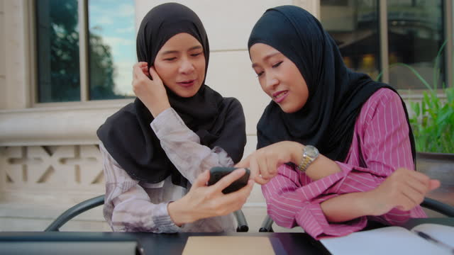 two asian women muslim friends taking a selfie while traveling at cafe in the city. two female looking down on to smart phone and talking having a good time together - two people stock videos & royalty-free footage