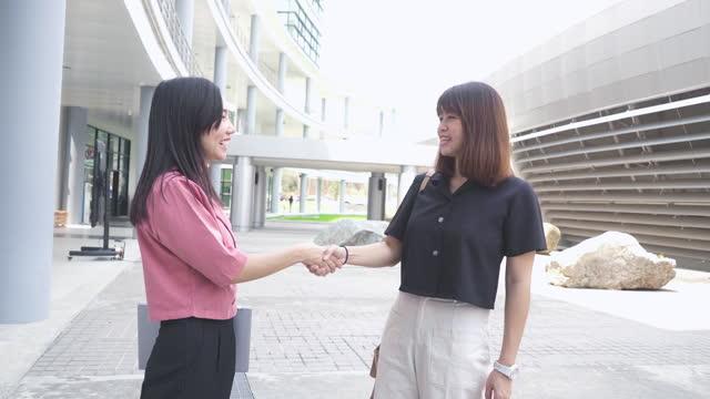 街の屋外で握手する2人のアジア人女性 - 向かい合わせ点の映像素材/bロール
