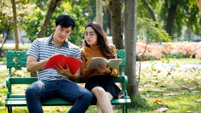 vidéos et rushes de deux jeune étudiante asiatique ou couple profitant d'est livre lecture et assis sur le banc dans le parc en plein air - banc