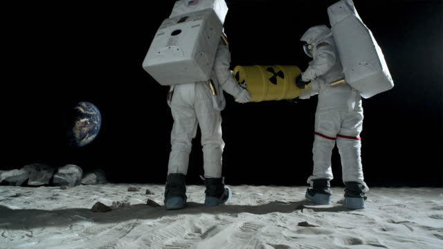 ws slo mo two astronauts on moon carrying container of radioactive material / berlin, germany - astronaut stock-videos und b-roll-filmmaterial