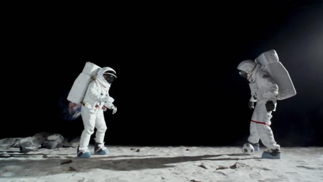 ws slo mo two astronauts on moon playing soccer / berlin, germany - 宇宙飛行士点の映像素材/bロール