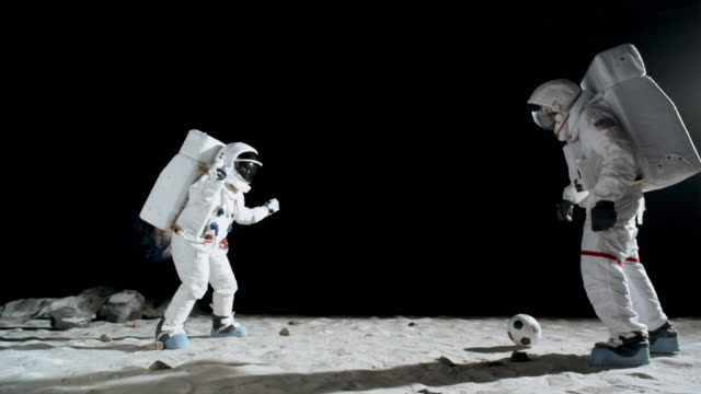 WS SLO MO Two astronauts playing soccer on moon / Berlin, Germany