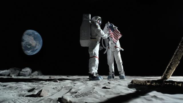 vídeos y material grabado en eventos de stock de ws slo mo two astronauts putting up american flag on moon and saluting / berlin, germany - astronauta