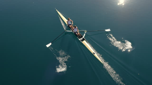 aerial two athletes in a coxless pair gliding across a lake in sunshine - two people stock videos & royalty-free footage