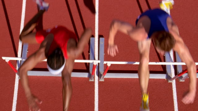 vídeos y material grabado en eventos de stock de two athletes jump over hurdles. - atlético