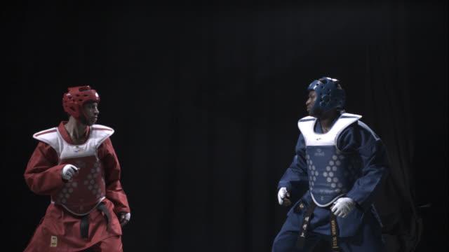 two athletes practice taekwondo in a studio. - taekwondo stock videos & royalty-free footage