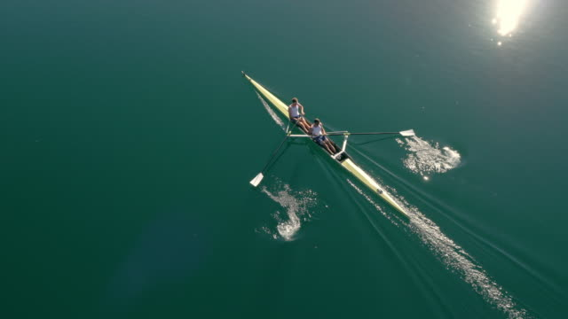 aerial two athletes rowing across a lake in a coxless pair on a sunny day - rowing stock videos & royalty-free footage
