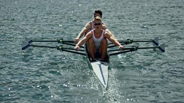 zwei athleten, die an einem sonnigen tag in einem doppelzweier wriggen - competition stock-videos und b-roll-filmmaterial