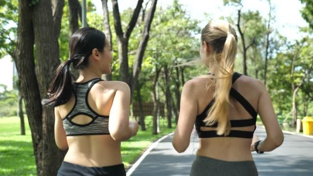 zwei sportliche frau, die im freien laufen im park, rückseite - verlust stock-videos und b-roll-filmmaterial