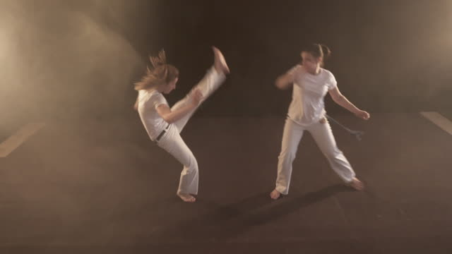 Two athletic women having a fight on capoeira sports training.