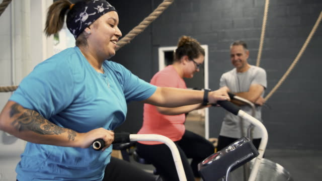 two attractive body-positive women, latino and caucasian, doing a workout on the exercise bike in the gym under the supervision of the coach, the senior 55-years-old cuban hispanic man - 55 59 years stock videos & royalty-free footage