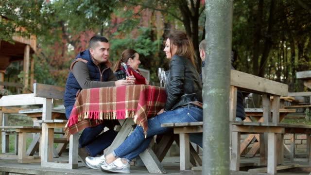 vídeos de stock, filmes e b-roll de duas atraentes casais sentado em uma mesa no restaurante café e comemorando lá fora com uma champanhe - fazendola