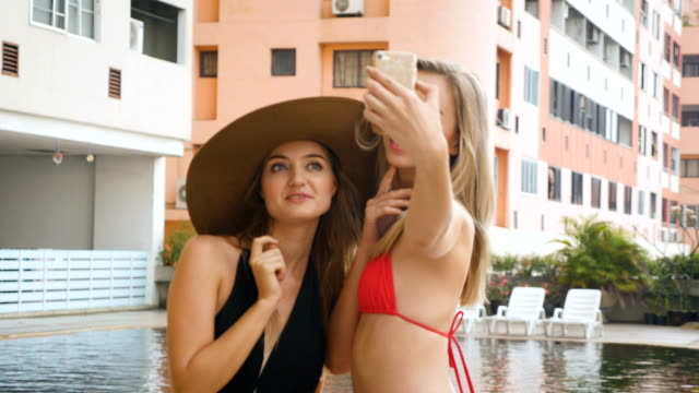 two attractive female friends taking a selfie next to a swimming pool, vacation, fun and relaxing concept - swimwear stock videos & royalty-free footage