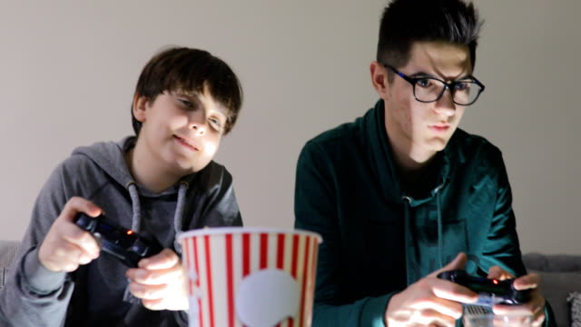 two attractive teenage boys are playing game console and smiling while sitting on the couch at home - gamepad stock videos & royalty-free footage