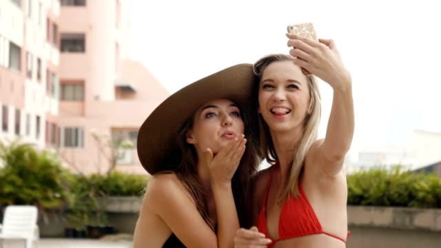 stockvideo's en b-roll-footage met twee aantrekkelijke womens gekleed in bikini nam selfie met smart phones bij zwembad - pardo