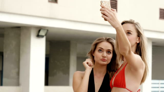 two attractive womens dressed in bikini was taking selfie with smart phones at pool - pardo brazilian stock videos & royalty-free footage