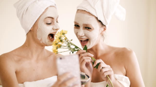 vídeos de stock e filmes b-roll de two attractive young women posing while taking selfie on the smartphone sitting inside spa room - spa