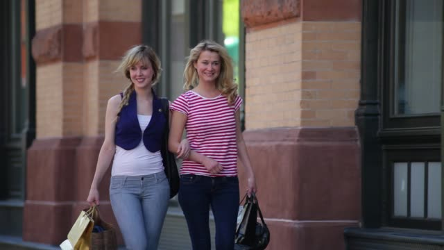 two attractive young women walk arm in arm along a sidewalk. - arm in arm stock videos and b-roll footage