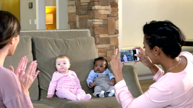 two babies on sofa, mothers photographing - close to stock videos & royalty-free footage