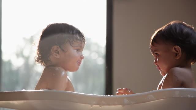 vídeos de stock, filmes e b-roll de two babies washing in a bathtub - só bebês