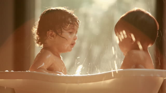 Two baby washing in a bathtub
