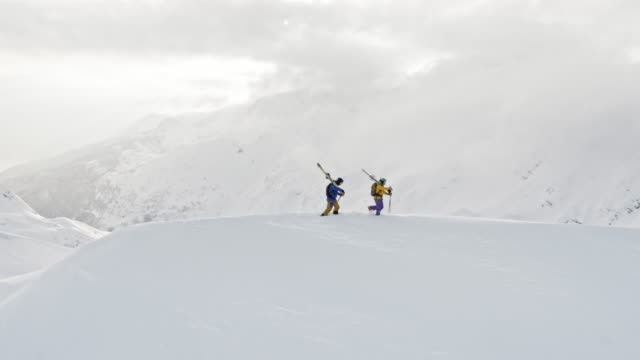 vídeos de stock e filmes b-roll de aerial two backcountry skiers carrying their skis along the mountain ridge - casaco de esqui