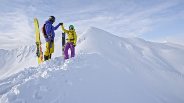 LD Two backcountry skiers doing a fist bump on a mountain ridge