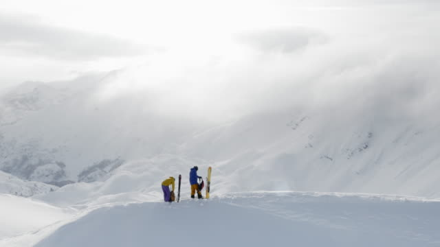 AERIAL Two backcountry skiers on a snowy mountain preparing for their descend