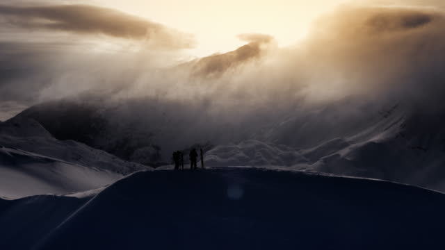 AERIAL Two backcountry skiers on the mountain top at sunset