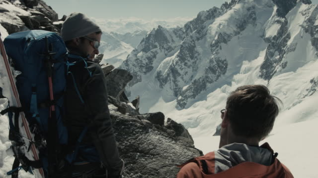 two backcountry skiers overlooking french alps, discussing routes, enjoying view. - male friendship stock videos and b-roll footage